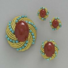 A set of pendant, earrings and ring, handcrafted in 18k yellow gold, showcases rich cabochon rubies and contrasting blue turquoises, rendering them smart classics.