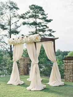 Pretty ceremony arbor with blush drapery. Arbor with Blush and cream flowers