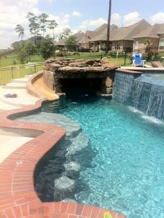 This is the lower pool, the shape is freeform, 89 perimeter feet and includes a custom gunite slide from the upper level, oversized grotto with bench seating, tanning ledge entry, swim up bar, 50 square foot hot tub raised above the waterline, pebble interior and large seating area overlooking Lake Houston, TX, overflow is 20 feet wide, deck moves down the hill from both sides and is wheel chair accessible on the left, all by Redman Pools, Inc. Houston TX www.redmanpools.com