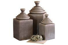 Three decorative canisters with pyramid shaped lids.