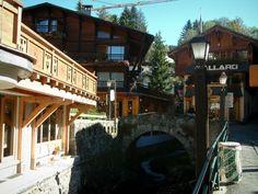 Megève: Lampioni, piccolo ponte di pietra che attraversa il fiume, negozi e case del paese (stazione di sport invernali ed estivi) - France-Voyage.com