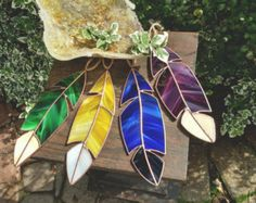 Perfect addition to any window on a sunny day! Collect a few and even make a dream catcher effect **price based on individual feather** These beauties are about 10in x 3in and come in loads of different colors depending on what you'd like! We also like to use a copper patina to give each feather that antique feel to it Our feathers are made by hand by my father and I with overwhelming good intention and smiles. Each one is uniquely itself- a colorful reminder even for when it isn't so…