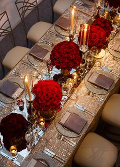 Everything from the pedestal vases to the mirrored runners reflected the romantic red of the roses and the soft glow of a seemingly endless array of candles. More images: http://www.colincowieweddings.com/articles/engagements-celebrations/sparkling-red-dinner-celebration