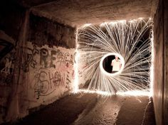 "ABURAKUASU - ""Firewire"" in which he is spinning steel wool that has been lit in a drainage tunnel in San Dimas. The stunning visuals were created with 00 grade steel wool on a string and captured on a Canon 60D with a Samyang 14mm lens. Believe it or not, there was no lighting equipment at the site or editing effects used in Photoshop. Amazing!"