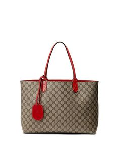 """One side is leather, reversible side is GG canvas. Leather shoulder straps, 7.4"""" drop. Removable ID tag. Open top. 11""""H x 15""""W x 4.4""""D. Made in Italy."""