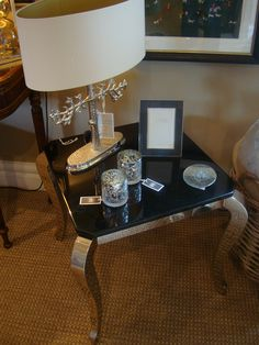 Black marble top table with silver lamp and accessories in the Richard Grafton Interiors Harrogate showroom.