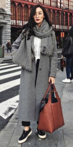 Levi + grey maxi coat + black jeans + white button up blouse + black and white gingham blanket scarf + black sneakers + large leather handbag + wide framed glasses. Brands not specified.