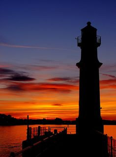 Edinburgh Harbour, Scotland lighthouse looms in silhouette as the last fiery rays of the evening sun paint the sky in a myriad of blazing color. Lighthouse Pictures, Lighthouse Art, Lighthouse Keeper, Landscape Silhouette, Beautiful Sunset, Beautiful Places, Le Moulin, Nature Pictures, Pretty Pictures