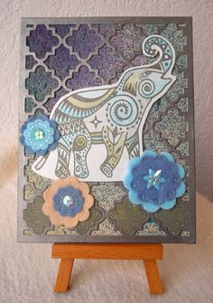 Michael Strong's large elephant stamp in soft watercolors over Papertrey's Quatrefoil Cover Plate die cut. It reminds me of the carved stone screens I saw in India. The felt flowers are Cuttlebug die cuts with sequins and embroidery.