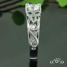 Palladium ring for center round diamond with double milgrained trinity knots on either side. There are 6 round emeralds set into the knots, and 2 round diamonds set into curls further down ring, with side face scroll engraving. Gem Diamonds, Round Diamonds, Celtic Knot Ring, Trinity Knot, Hand Engraving, Jewelry Box, Emerald, White Gold, Wedding Rings