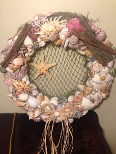 The styrofoam wreath was covered in burlap and seashells from Siesta Key and Sanibel Island were glued onto the Wreath. Spanish moss, netting