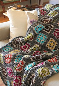 Crocheted snuggly loveliness. I want one of these with chocolate brown as the base and hunter, burgundy, and gold as the other colors.