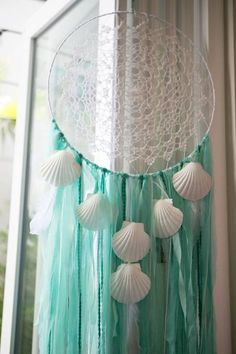 """Two turquoise yarn and chiffon dreamcatchers with white seashells and dusted feathers, featuring tiny flecks of fluorescent teal and white glitter. Small 12"""" diameter x 38""""l Large 19"""" diameter x 60""""l"""