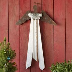 "ARCHITECTURAL ANGEL -- Fashioned entirely of reclaimed materials, our nostalgically evocative angel boasts a robe of vintage boards salvaged from buildings being demolished, a yoke of pressed tin, rustic tin wings and a wire halo. Handmade in USA. Catalog exclusive. 18""W x 1-1/2""D x 32""H."