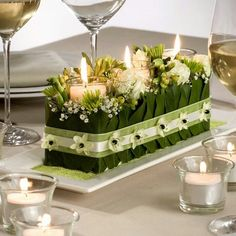 candle centerpiece - 3 candles glass cylinders pushed into green oasis holes , add white Lilly of valley, add Lilly leaves, add ribbon to hold together