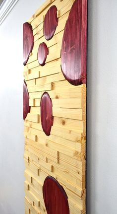 Hi, welcome to Stains and Grains, custom wooden wall art. Size: 48h X 16w This piece of wood wall art is meant to convey the liquid motion of a lava lamp. The contoured horizontal rows are done in natural stain, and the sandpaper-molded globs are in a bright red cabernet color. The #liquidsandpaperstains