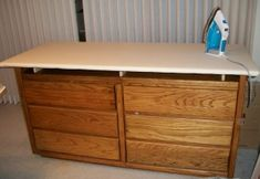 An old dresser combines notions storage with an ironing board / pressing station.