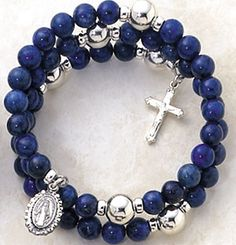 This is a stunning full five decade Lapis rosary on a wrap around bracelet.  The Hail Mary beads come in a 6mm bead Lapis semi-precious gemstone.  The Our Father beads are 8mm Sterling Silver with rondelles on either side.  Sterling silver Miraculous Medal attached at one end of the bracelet and a sterling crucifix at the other end.  This bracelet fits all and is quite unique as the bracelet coils apart so it easily fits around the wrist.  Each bracelet comes in a beautifully black flocked…