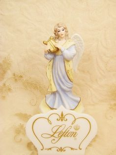 Vintage Angel Harp Music Box Figurine plays Waltz of the Flowers.  Angel is playing the harp dressed in a baby blue gown and a yellow scarf.  The base is decorated with a yellow ribbon which drapes ar