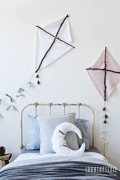 Mooie vliegers van stof en takken aan de wand. Simpel maar mooi idee voor de kinderkamer.