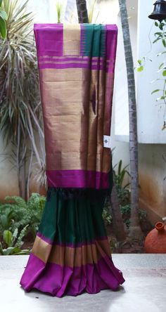 A CLASSIC DARK GREEN KANCHIVARAM SAREE WITH A PLAIN BODY IS ENHANCED BY AN INTERESTING BRIGHT PURPLE PALLU WITH TEMPLE BORDERS. THE SAREE IS FINISHED BY A GRAND ZARI PALLU.