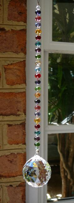 """We created this Swarovski crystal sun catcher with the intention that the strand be as much a focal point as the pendant. And it definitely is. It is sparkly and colorful!  We suspended a clear 30mm Swarovski crystal ball from a 5½"""" glistening strand of Swarovski crystal briolettes in 14 colors interspersed with clear Swarovski beads. The entire length, including the 1¼"""" loop hanger, is over 9"""" inches. ★ Photos are enlarged to show detail. Please check measurements carefully.  We use only…"""