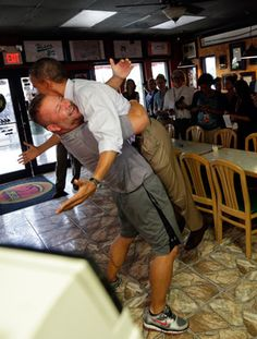 Scott Van Duzer, owner of the Big Apple location next to Indian River State College in Fort Pierce, lifts President Obama in a bear hug as he stops for pizza on his re-election campaign trail.