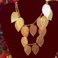 Two tier gold plated decorative leaf necklace This necklace is gold plated and has two tiers of decorative gold leaves which are on a gold plated chain. It has. A gold plated lobster clasp on the chain. The necklace is very pretty with suits or a nice turtle neck and slacks. Jewelry Necklaces