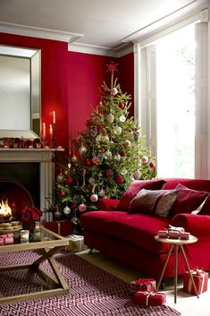 Shades of deep red, a real tree and a roaring fire create a perfect Christmas living room scheme. Combine with touches of gold and white to bring depth and sparkle. Added ambiance come from lit candles around the room.