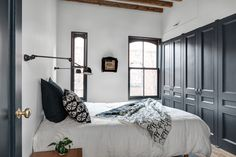 Wall-mounted Jieldé lamps (about $860 for the pair at Horne) flank the bed in the master bedroom. A wall of closets is concealed by doors painted Farrow & Ball's Off Black.