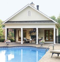 The outdoor fireplace under the covered porch of this pool house makes this backyard perfect for year-round enjoyment. | Photo: Laurey W. Glenn | myhomeideas.com