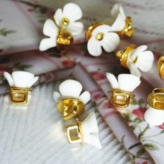 This is a lot of 12 Cute tiny flower buttons with shanks for sewing, for dainty jewelry making, and for creating embellishments and accessories.These buttons have very large and square 8 mm shanks.- 10 mm- White and gold colors.- Made from res... Button Flowers, Tiny Flowers, Fancy Buttons, Dainty Jewelry, Vintage Brooches, Embellishments, Jewelry Making, Sewing, Colors