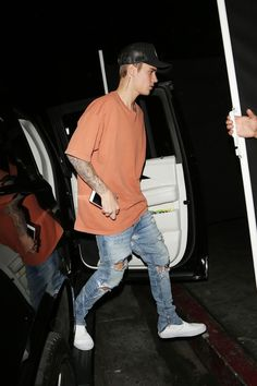 Justin Bieber wearing  Vans Premium Leather Slip-Ons, Rip Curl Hawaii Trucker Hat, Fear of God 4th Collection Selvedge Denim Vintage Indigo Jean