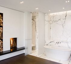 Stunning minimalist bathroom with simple wood burning fireplace next to stacked shelves filled with chopped firewood over a raised hearth finished with a sleek black top. Bathroom Fireplace, Freestanding Fireplace, Freestanding Tub, Modern Fireplace, Fireplace Design, Fireplace Ideas, Minimalist Fireplace, Salons Cottage, Marble Wood