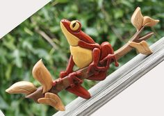 "Tree Frog Intarsia Wall Hanging. Dimensions are approximately 12"" by 7.5"". The wood used in the photographed item is padauk American cherry, yellowheart, wenge, and black walnut. Finished with clear lacquer. Contains 27 segments of wood. A hanger is attached to the back. AUD $79.60."