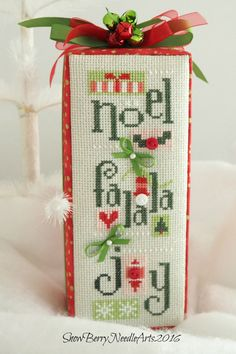 Three happily festive Christmas words decorate the cross stitched front of this table decoration. Bright and colorful, this Noel, Fa La La and Joy fabric covered box is ready to become part of your holiday display. ~~DETAILS~~ * this stitchery is what I refer to as Second Chance Stitchery. It is a piece that has not been stitched by me but rather purchased and refreshed into a fun finish by me. This Lizzie Kate design has been expertly stitched using a seasonal palette of colors on a…