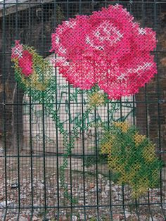 Rose cross stitched on fence.  This image was added to tumbler by Makin'ology, who found the image on the punto croce club on Facebook.