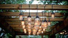 I love the homemade mason jar lights hanging from the pergola. Now I just need some jars and lights and pergola wood. Dan take note, happy wife happy life Pergola Lighting, Outdoor Lighting, Exterior Lighting, Outdoor Chandelier, Pergola With Lights, Dramatic Lighting, Landscape Lighting, Modern Lighting, Garden Lighting Ideas