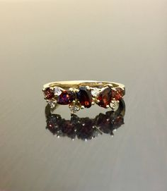 DeKara Designs Collection Our latest design! An elegant and lustrous garnet diamond wedding/engagement band.  Metal- 18K Yellow Gold, .750.  Stones- 3 Oval Garnet, 2 Pear Shape Garnets, 5 Round Diamonds F-G Color VS1 Clarity, 0.10 Carats. Latest of my creations. A beautiful 18K Rose Gold Garnet Diamond Engagement Band. There are three fiery oval garnets, as well as two pear shaped garnets, that are all professionally set in between four prongs. There are five prong set diamonds in betwee...