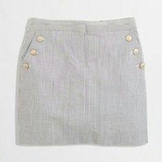 """J. Crew Factory Gray Striped Seersucker Mini Skirt J. Crew Factory skirt, size 12, in excellent condition! Perfect spring and summer skirt! Grayish blue and white vertical seersucker stripes with three button details on each pocket. Zipper and tab button in front. Also has back pockets. Only flaw is minor wear/patina on buttons. 17"""" waist and 15"""" length. Cover photo from J. Crew Factory website. Please ask any and all questions before purchasing. No trades. Made a reasonable offer. Thanks…"""