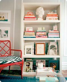 Il colore delle copertine dei libri e quello della poltroncina illuminano il bianco della libreria