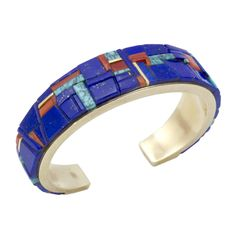 This amazing 14k gold Charles Loloma bracelet is inlayed with lapis, gem quality Lone Mountain turquoise , and Mediterranean coral.  Measures 5 1/4″ with a 7/8″ opening.  3/4″ width.