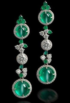 A pair of cat's eye emerald and diamond pendent earrings Each formed as a series of three 'target' design plaques, two of which are set with a round cabochon cat's eye emerald surrounded by a row of brilliant-cut diamonds, the central plaque set with a brilliant-cut diamond with similar surround, all joined by brilliant-cut diamonds and circular-cut emeralds to multi-tiered settings, mounted in 18k white gold.: