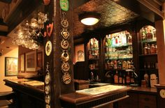 English Pub inspired basement. The dark, brown wood and tin ceilings epitomize the English pub vibe.