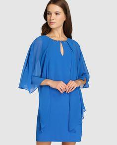 Vestido corto, en color azulón, con capa superpuesta. Tiene escote redondo con abertura y pedrería tipo collar.