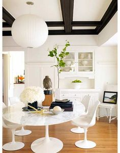 """""""The dining room is all about the box-beam ceiling,"""" Hom says. """"I thought it was important to play off that."""" The large George Nelson Bubble lamp does a great job of attracting attention. Knoll's Saarinen marble table and Tulip chairs are """"pleasingly thrown off"""" by the worn vintage chair in the corner.   - HouseBeautiful.com"""