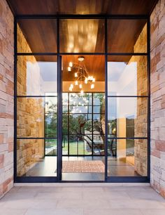 Spanish Oaks Contemporary House   Front Door   Paula Ables Interiors   Continuous stone wall leads to Foyer   Two large Steel Window / Door units allow you to see through to the Backyard   Texas Hill Country Contemporary Design