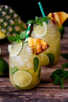 Pineapple Ginger Mojitos with Spiced Rum - a sweet and spicy twist on the classic mojito cocktail. Served with a wedge of caramelized pineapple. #cocktailrecipes