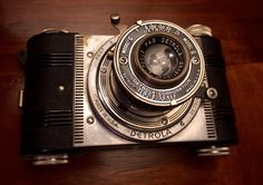 Deutrola, Model G, 1938-40. Bakelite plastic camera. It was a less expensive alternative to the model H. The more expensive Detrolas had metal viewfinder housings, the flimsy molded-plastic viewfinder of the G is often found warped or disintegrated entirely. (Note there is no viewfinder on mine) The Model G was affordably priced from $9.95 to $12.50. The carrying case was extra priced around $3.49.