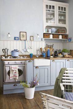 Nie biel, lecz miętowy błękit dominują w kolorystyce tej kuchni. To ciekawa wariacja na temat stylizacji prowansalskiej. Jej klasyczny charakter podkreślają liczne rustykalne dodatki oraz malowane meble.